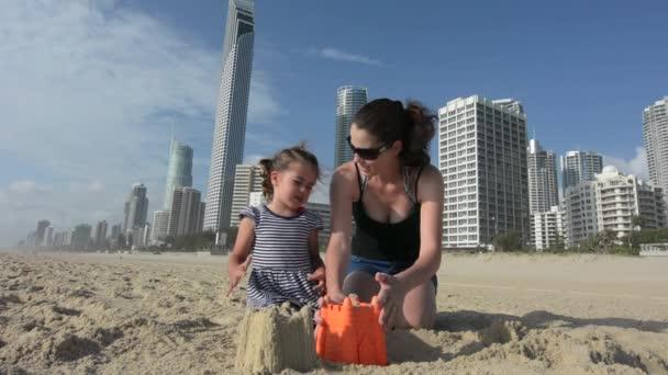 Anya és lánya épít homokvárat, Surfers Paradise, Ausztrália