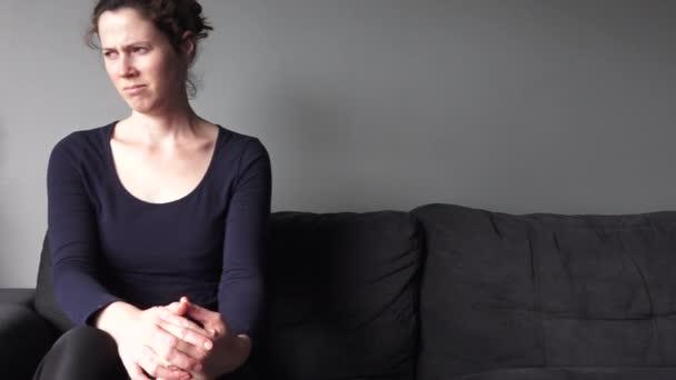 Frau in ihren Dreißigern sitzt aufgebracht auf einem Sofa.