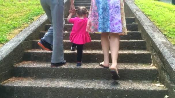 Malá holčička vylézt nahoru po schodech s její matkou a babičkou