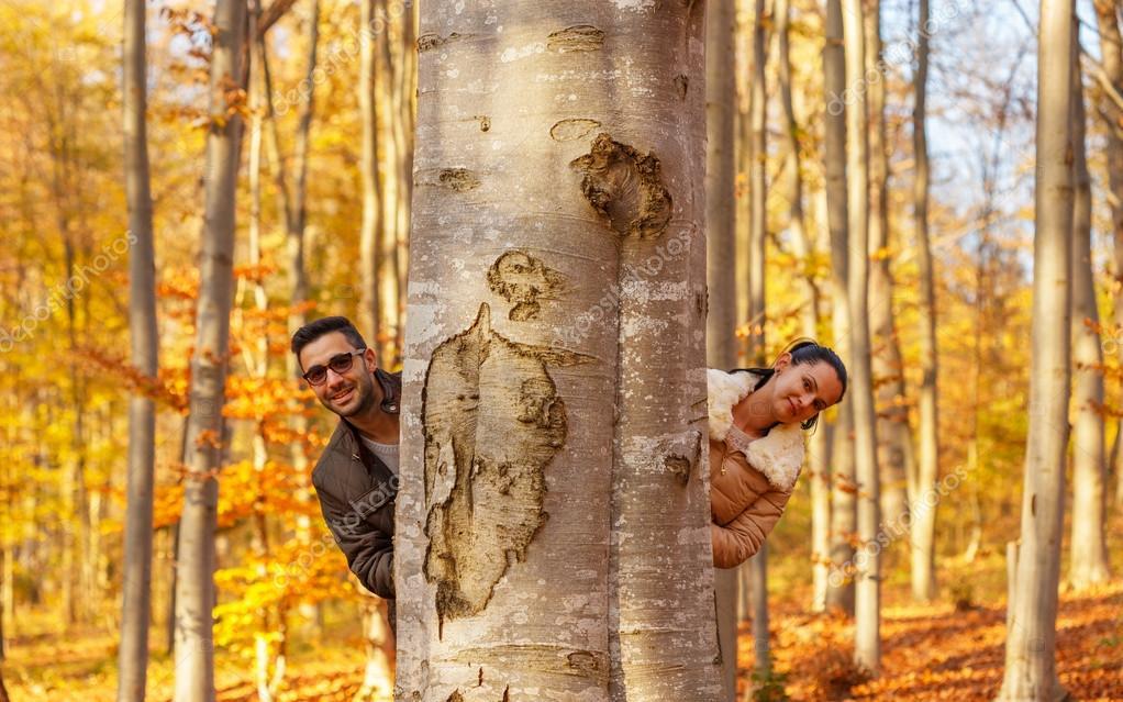 Влюбленные мило улыбаясь за дерево — стоковое фото