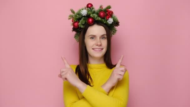 Šokovaný úsměv roztomilé mladé ženy ve vánočním věnec pohled ukazuje dvě strany na pracovní ploše, ukazující palce nahoru jako gesto, izolované na růžovém pozadí studia. Šťastný Nový rok oslavy veselé dovolené