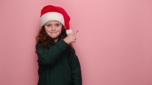 Roztomilá holčička ukazuje ukazováčkem na volné místo pro reklamní obsah, oblečený v červeném vánočním klobouku a svetru, izolované přes růžové pozadí. Nový rok oslavy veselé prázdniny koncept