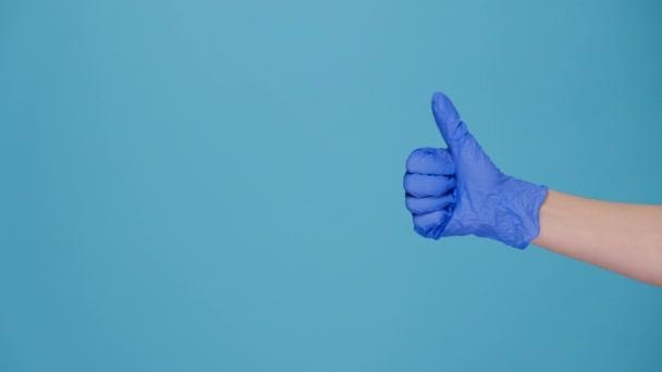 Nahaufnahme von nicht wiederzuerkennenden Frauen in medizinischem Latex-Handschuh macht Daumen hoch Geste, zeigt Zustimmung oder Zustimmung, isoliert auf blauer Wand mit Kopierfläche für Werbung. Handzeichen. Geste wie Geste