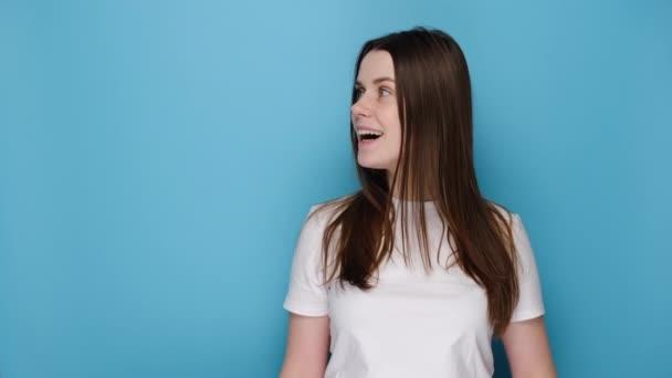 Aufgeregt lächelt eine junge kaukasische Frau in weißen T-Shirts, während sie den Papierpfeil zur Seite zeigt, isoliert auf blauem Hintergrund mit Kopierfläche für Werbung. Menschen-Emotion-Konzept