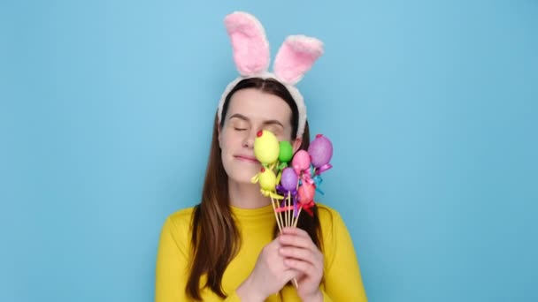 Portrait of good looking optimistic young woman with bunny fluffy ears, has a happy look, holds painted eggs on sticks, stands over blue studio background with copy space on right for your text