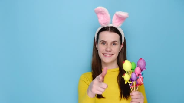 Fiatal izgatott nő lány 20-as rózsaszín nyuszi bolyhos fülek, azt mondják, hé nézel mutató ujjal másolni helyet félre munkaterület, kezében kis tojás, elszigetelt kék háttér stúdió. Húsvét fogalma