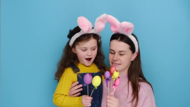 Big day is coming up. Surprised shocked mother with cute daughter to have much work preparation to Easter, holding paints eggs, isolated on blue studio background. Rejoice spring and holidays concept