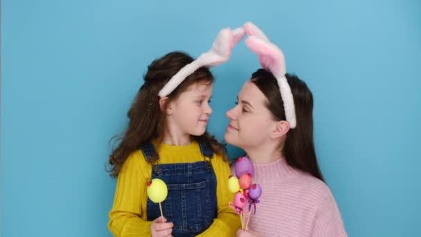 Veselé Velikonoce. Potěšení matka a dívka dítě v zajíček nadýchané uši nosit barevné vejce, polibek a hrát společně, připravit na jarní svátky, mají velikonoční aktivity, izolované na modré zdi