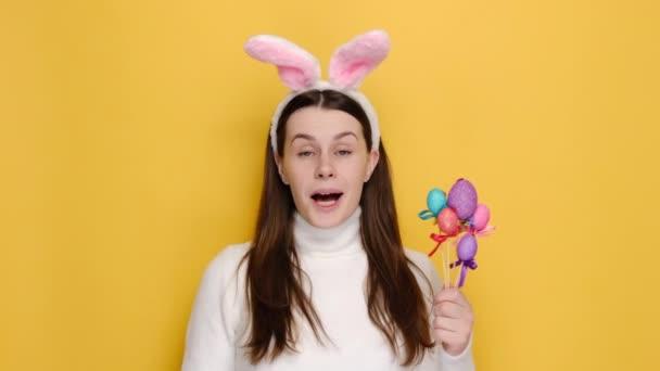 Vidám meglepett fiatal nő rózsaszín nyuszi bolyhos fülek mutat megkérdőjelezhető kifejezés, kérdezi úgy érted nekem, hordozza a kis húsvéti tojás, visel fehér pulcsi, elszigetelt sárga stúdió háttér