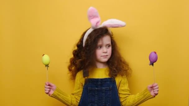 Portré meglepett kislány rózsaszín nyuszi bolyhos fülek kezében két színes tojás, hogy szimbóluma a vallási ünnep, elszigetelt sárga háttérrel. Gyermekkori életmód és boldog húsvéti koncepció