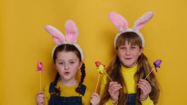 Vicces aranyos húgok rózsaszín nyuszifül stúdió elszigetelt sárga háttér néz pozitívan a kamera, tartja és fedi a szemét színes tojás. Gyermekkori életmód és boldog húsvéti koncepció
