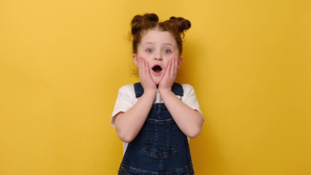 Portrait of surprised little preschool girl look at camera feel stunned amazed by unexpected good news, happy cute small child shocked by unbelievable surprise, isolated on yellow studio background