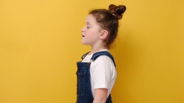 Profil Seitenansicht von glücklichen kleinen Vorschulmädchen tun tiefen Atem genießen frische Luft oder träumen füllen mit Energie Gefühl gesund gutes Konzept, isoliert auf gelbem Studiohintergrund mit Kopierraum