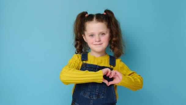 Kellemes kinézetű mosolygós kislány gyerek alakítja szív gesztus felett mellkas, bájos elégedett cutie mutató szerelem jele, elszigetelt kék stúdió háttér fénymásolás. Az emberek érzelmei