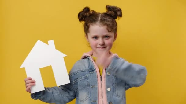 Beautiful little preschool girl holding small paper white house model with thumb up like gesture, wears denim jacket, isolated over yellow background wall with copy space. Housing and mortgage concept