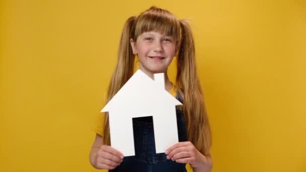 Detailní portrét krásně se usmívající kavkazské holčičky držící malý papírový bílý domov, přátelský dívající se do kamery, model přes žluté pozadí studia. Rodinný dům, bydlení a hypoteční koncept