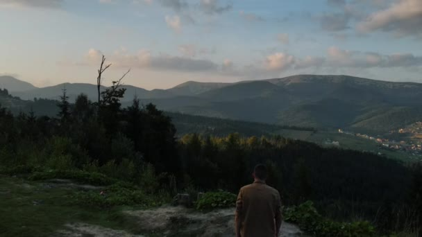 Drone shot of millennial young man climbing uphill on background beautiful mountain landscape during sunset. Travel concept. Contemporary traveler outdoors walking on amazing natural trekking path
