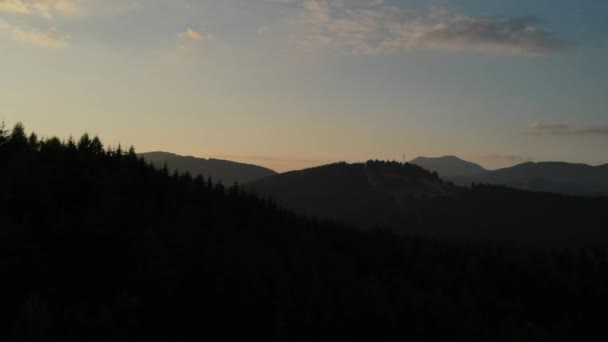 Aerial drone shot of amazing dramatic orange sunset or sunrise evening over beautiful calm mountains in countryside. Silhouette pine forest. Travel destination inspiration for romantic escape concept