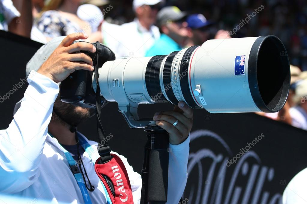 A photojournalist uses a Canon telephoto lens to capture action at Australian Open 2016