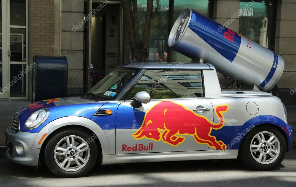A Red Bull Mini Cooper Publicity Car With A Can Of Red Bull Drink