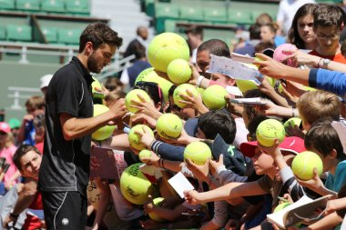 Professional tennis player Gilles Simon of France signing autographs after practice for Roland Garros 2015