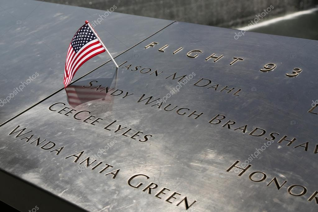 american flag left at the national september 11 memorial at ground