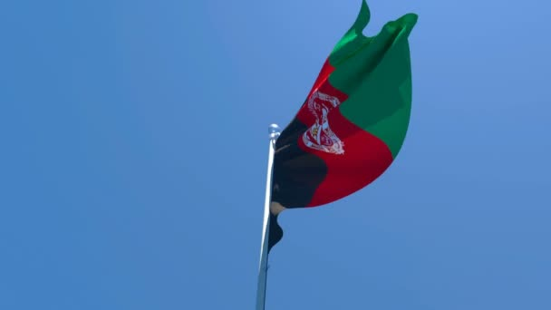 The national flag of Afghanistan is flying in the wind against a blue sky
