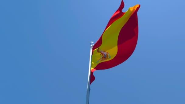 Spanyolország nemzeti zászlaja a szélben repül a kék ég ellen.