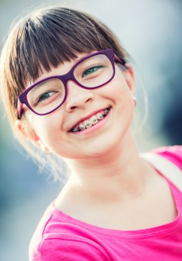 Girl. Teen. Pre teen. Girl with glasses. Girl with teeth braces. Young cute caucasian blond girl wearing teeth braces and glasses