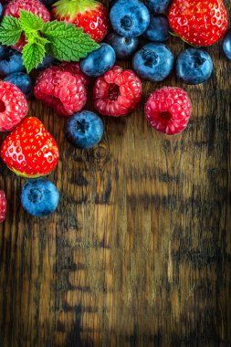 Berry fruits on wooden background or table. Blueberries, raspberries, strawberries, Forest fruits.