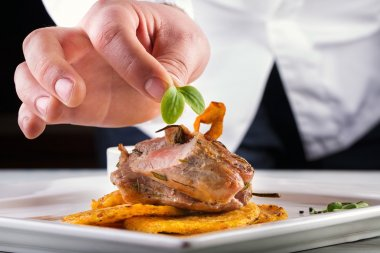 Chef in hotel or restaurant kitchen cooking, only hands. Prepared meat steak with potato or celery pancakes.