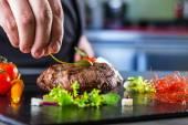 Šéfkuchař v hotelu nebo restaurace kuchyně vaření, pouze ruce. Připravené hovězí steak s rostlinné dekorace