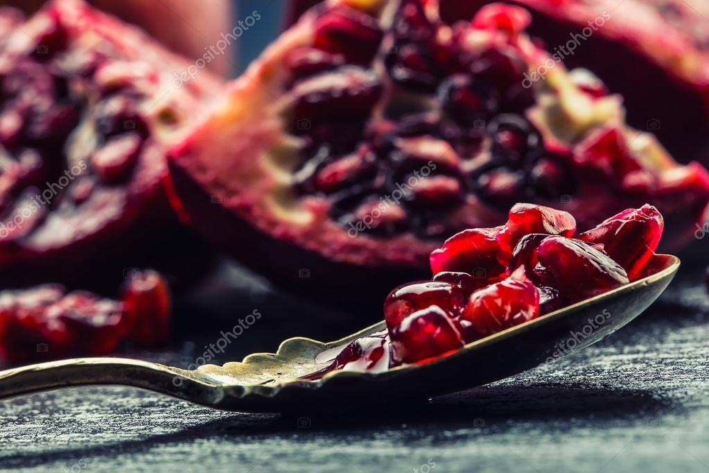 Pieces and grains of ripe pomegranate. Pomegranate seeds. Part of pomegranate fruit on granite board and antique spoon.