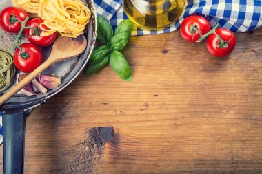 Italian and Mediterranean food ingredients on wooden background.Cherry tomatoes pasta, basil leaves and carafe with olive oil. Wooden and old kitchen utensils. Old kitchen pan stock vector