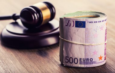 Euro currency. Court gavel and rolled Euro banknotes. Representation of corruption and bribery in the judiciary.