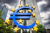 Symbol měny euro se temné mraky sídle Evropské centrální banky ve Frankfurtu nad Mohanem, Německo