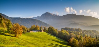 Beautiful autumn landscape with traditional farm house in the Alps