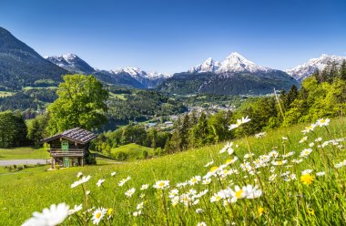 Idyllic mountain landscape in the Alps with traditional mountain lodge in springtime