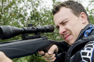 A man holding a rifle and takes aim