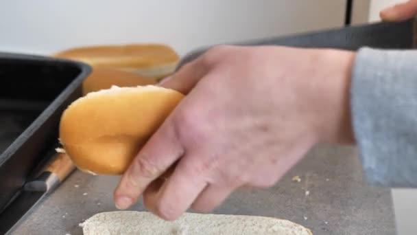žena krájí rohlíky pro hot dog a dává do misky