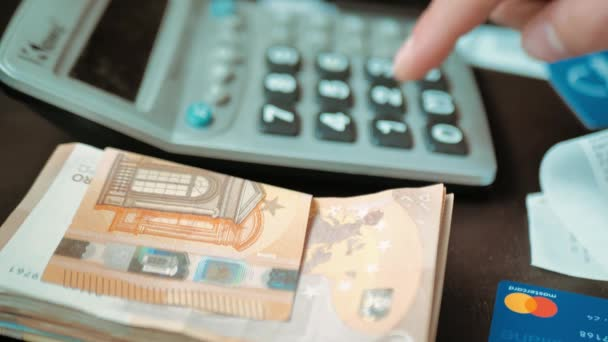 Male hand counts expenses or income on a calculator