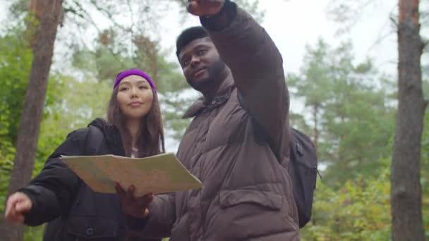 Multiracial tourists on trek navigating with map