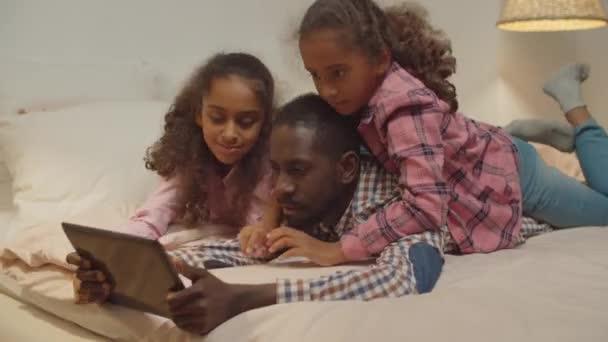 Afrikai apa gyerekekkel megosztani tabletta pc az ágyban