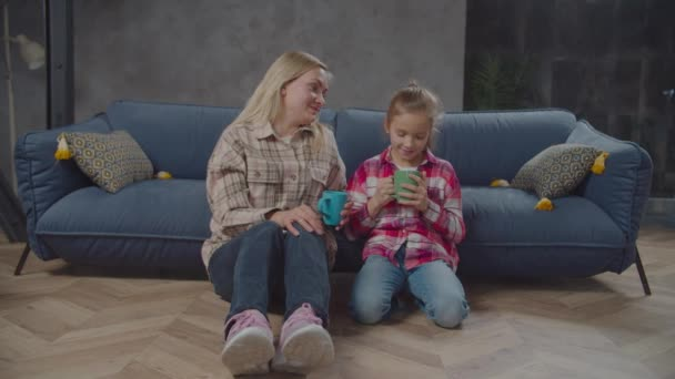 Pozitivní maminka a roztomilá dcera pití čaje uvnitř