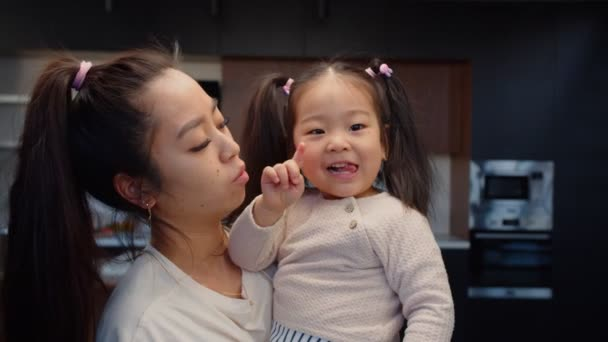 Smiling happy asian mother holding toddler daughter
