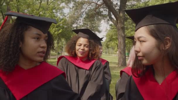 Mosolygós fekete diák portréja akadémiai ruhában a diplomaosztón