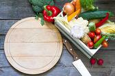 Čerstvá zelenina a prázdné prkénko na dřevěné pozadí