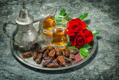 Tea, dates fruits and red rose flowers. Oriental hospitality vin