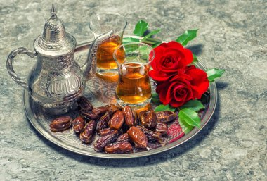 Tea, dates fruits and red rose flowers. Oriental hospitality con