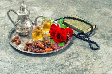 Tea, red rose flower, dates, holy book quran and rosary. Islamic